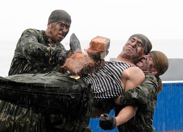 A Russian soldier crushes a pile of bricks with a hammer on the stomach of a fellow soldier during a performance as part of a naval parade rehearsal at Vladivostok's harbour